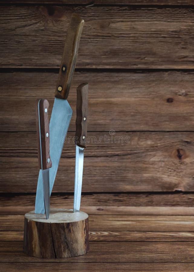 Cuchillos de cocina pegados en un soporte de madera imágenes de archivo libres de regalías