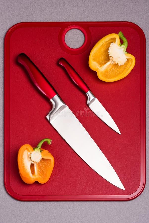 Cuchillos de cocina rojos en tabla de cortar roja con pimientas imagenes de archivo