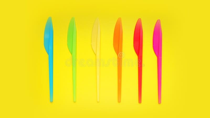 Cuchillos plásticos violeta, naranja, amarillo, azul, rojo aislada en el amarillo imagenes de archivo