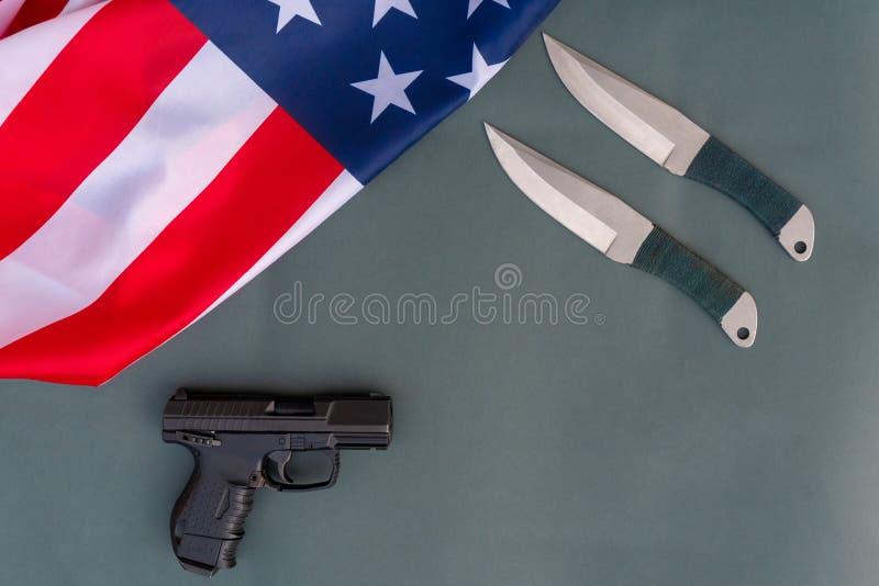 Cuchillos que lanzan, pistola, endecha del plano de la bandera americana en fondo gris Estados Unidos disparan contra leyes - los fotos de archivo