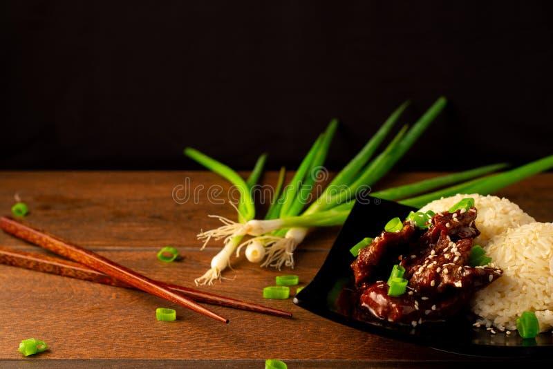 Cucina asiatica di manzo e riso con bacchette e sfondo nero fotografia stock