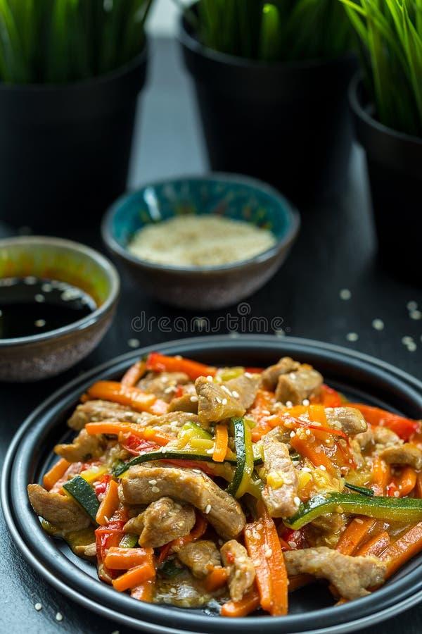 Cucina cinese - carne di maiale con le verdure fritte nel grasso bollente in salsa Acido-dolce immagini stock libere da diritti