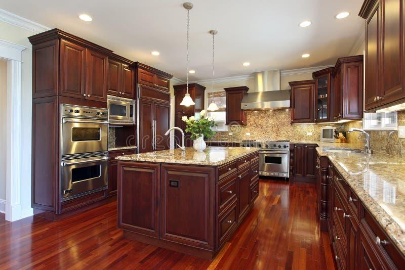 Cucina con cabinetry di legno della ciliegia fotografie stock libere da diritti