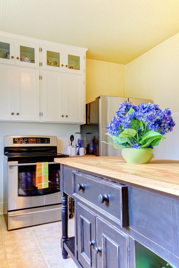 Cucina con l'isola nera e gli armadietti bianchi. fotografia stock