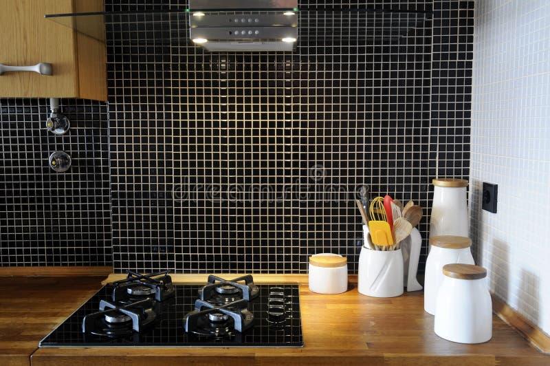 Cucina con le mattonelle nere lustrate ed il contatore di legno fotografia stock libera da diritti