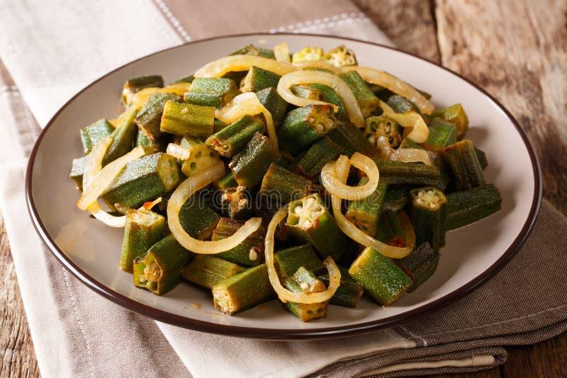 Cucina del vegano: il gombo piccante ha fritto con il primo piano della cipolla su un piatto fotografia stock