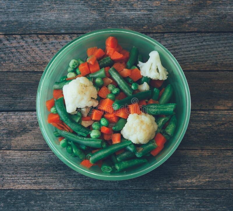 Cucina dell'asiatico del piatto miscela di verdure delle carote, dei piselli, dei fagiolini e del cavolfiore in una ciotola verde immagine stock