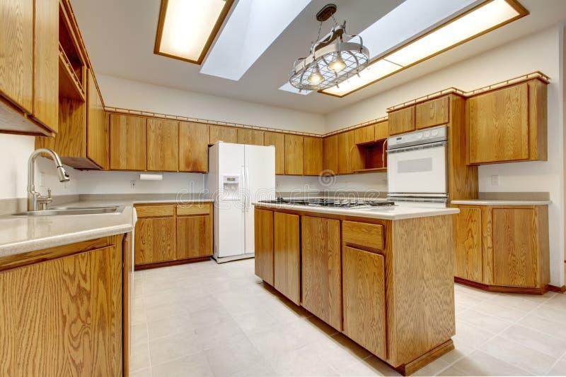 Cucina di legno con l'isola senza finestre con indicatore luminoso luminoso. immagine stock