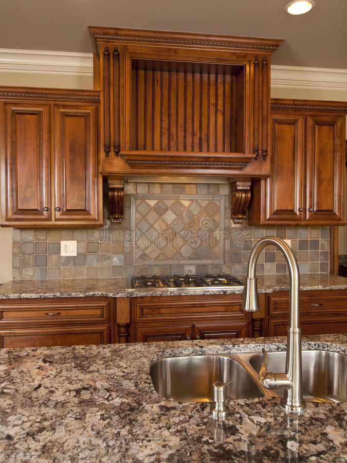 Cucina di legno scura domestica di lusso con il rubinetto fotografia stock libera da diritti