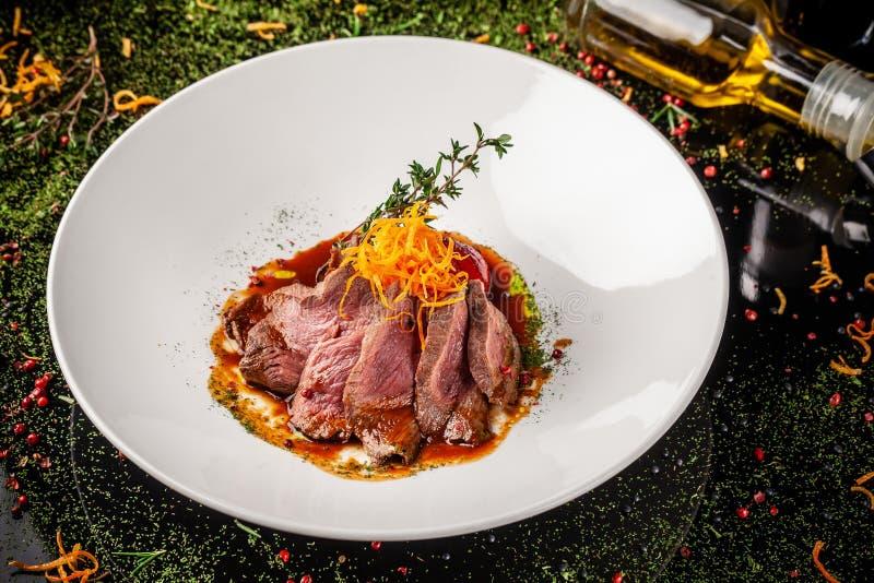 Cucina europea Vitello marinato con raro di medium dell'arrosto Grado di tostatura Il cuoco unico versa l'olio d'oliva del manzo  fotografie stock
