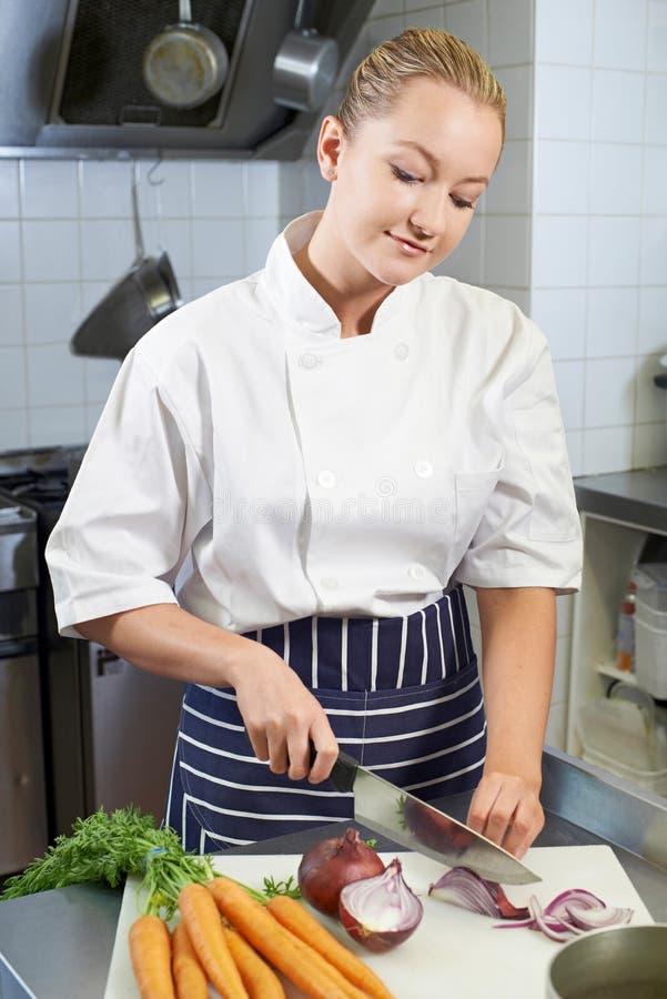 Cucina femminile del ristorante di Preparing Vegetables In del cuoco unico fotografia stock