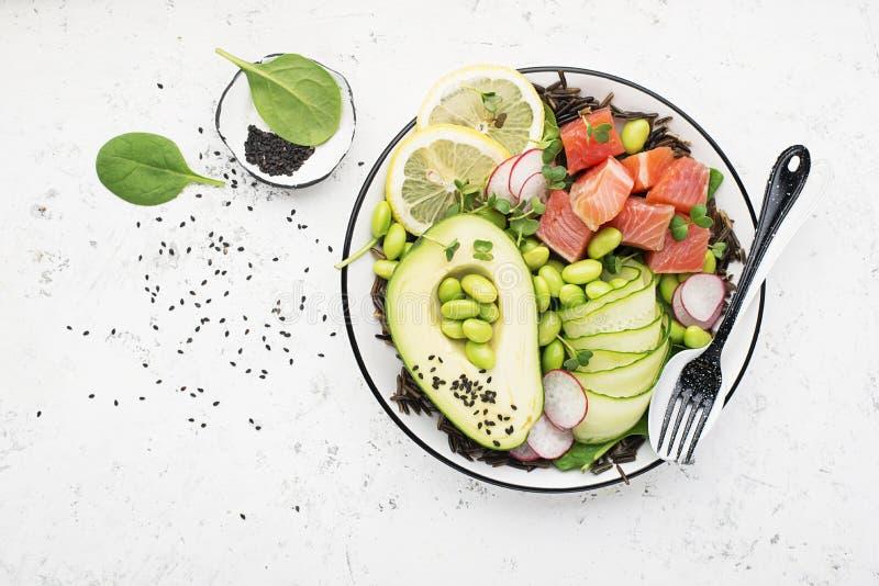 Cucina fresca dei frutti di mare Colpisca una ciotola di salmone, l'avocado, la soia, i cetrioli, il ravanello, i micro verdi, il fotografia stock