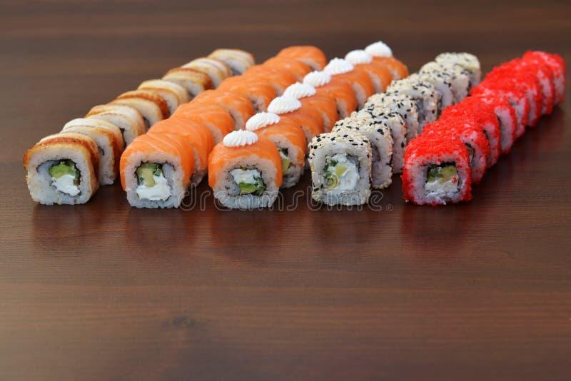 Cucina giapponese - sushi di stile di approvvigionamento del buffet metta in ristorante - Maki Sushi e sushi di color salmone di  immagini stock