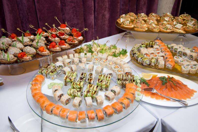 Cucina giapponese - sushi di stile di approvvigionamento del buffet metta in ristorante - Maki Sushi e sushi di color salmone di  immagine stock libera da diritti