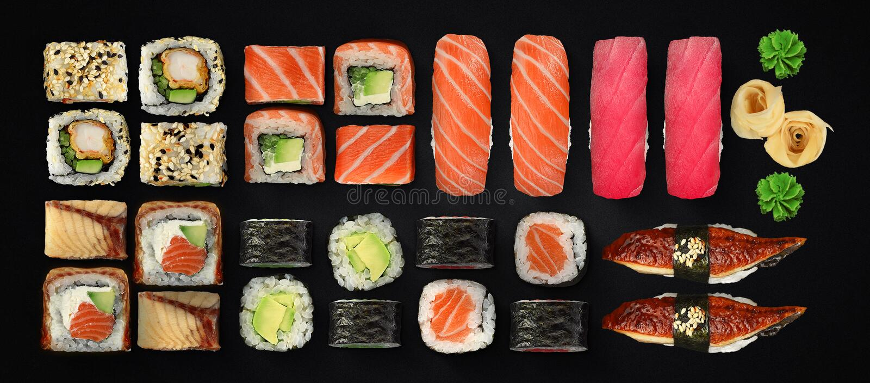 Cucina giapponese Sushi e rotoli messi sopra fondo scuro immagini stock libere da diritti