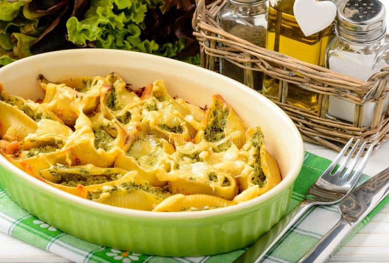 Cucina italiana - coperture della pasta farcite con spinaci, la ricotta e al forno con il pomodoro immagine stock