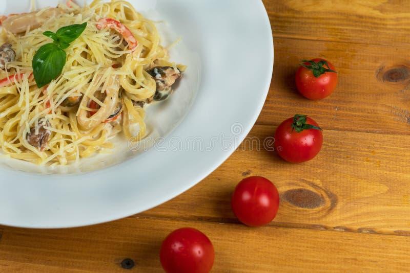 Cucina italiana dell'alimento del basilico del formaggio dei pomodori della pasta dei frutti di mare fotografie stock libere da diritti
