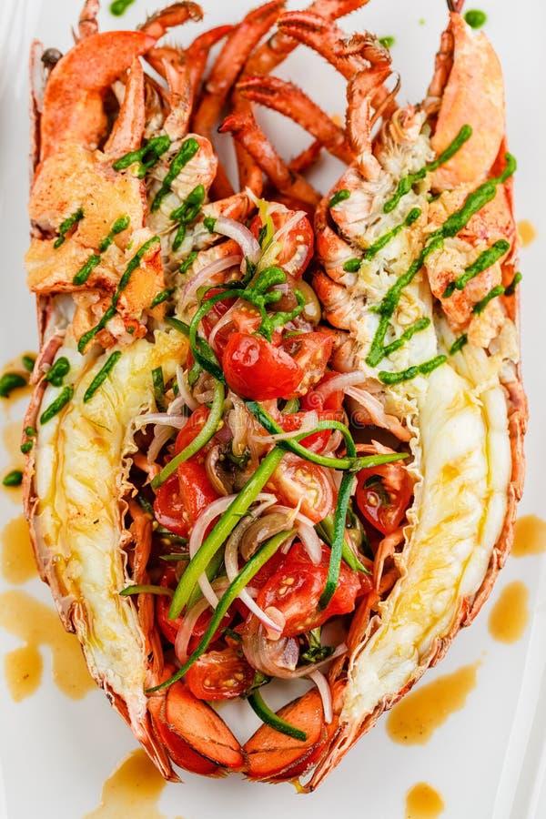 Cucina italiana L'intera aragosta al forno ed affettata a metà è servito con l'insalata e la salsa del pomodoro sul piatto bianco immagine stock libera da diritti