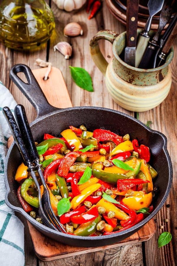 Cucina italiana, peperonata: peperone dolce arrostito con i capperi ed il basilico fotografia stock libera da diritti