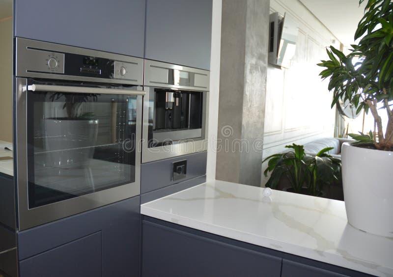 Cucina moderna con il forno elettrico, la stufa eclettica e la macchina del caffè fotografia stock libera da diritti