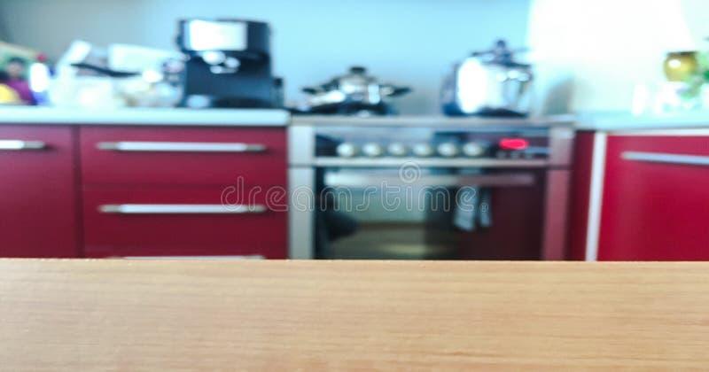 Cucina moderna con il ripiano del tavolo e spazio per voi Piano d'appoggio di legno vuoto sul fondo della finestra della cucina d fotografia stock