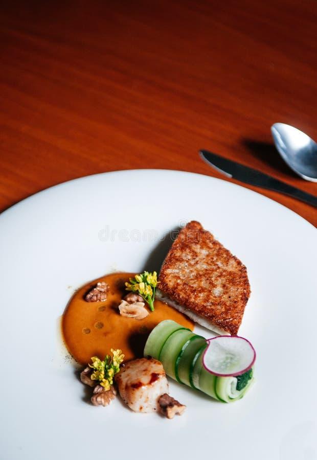 Cucina moderna della bistecca del pettine e della spigola, spigola arrostita e pettine con salsa crema sul piatto bianco, vista s fotografia stock libera da diritti