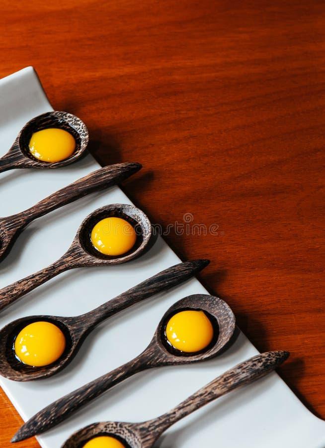 Cucina moderna di creatività molecolare della gastronomie, dessert della gelatina in cucchiai di legno sul piatto bianco fotografie stock