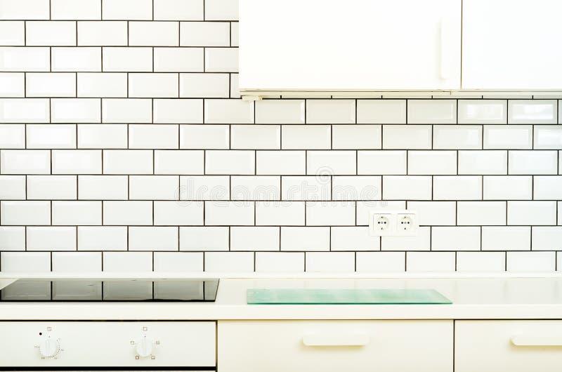Cucina moderna e minimalista bianca di interior design, di stile con gli elettrodomestici Spazio aperto in salone in pieno di immagine stock libera da diritti