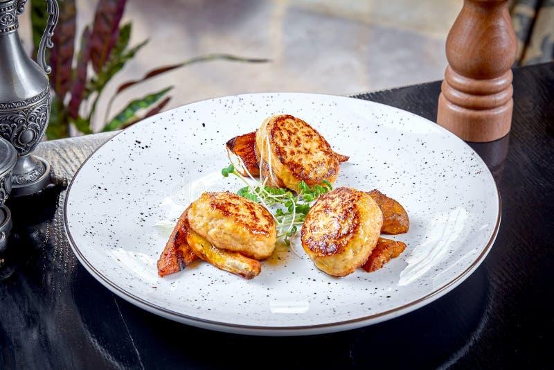 Cucina moderna Vista alta vicina sulla cotoletta servente reastaurant da coniglio sulla carota arrostita con micro verde sul piat fotografia stock libera da diritti
