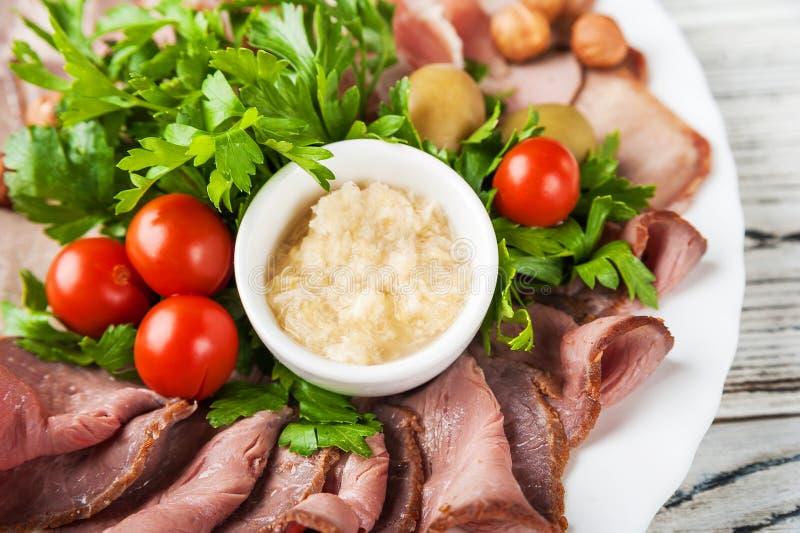 Cucina nazionale russa Pomodori marinati, carne tagliata, olive, prezzemolo Salsa di rafano Primo piano dell'insalata su un piatt fotografie stock libere da diritti
