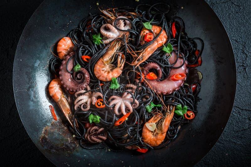 Cucinando gli spaghetti neri con frutti di mare fatti del polipo, gamberetti della tigre immagini stock libere da diritti
