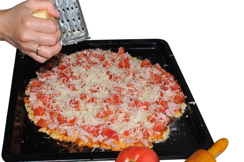 Cucinando pizza a casa Pizza con il prosciutto, i pomodori ed il formaggio grattugiato fotografie stock libere da diritti