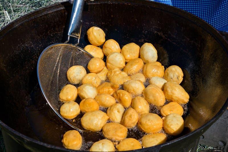 Cucinando in un alimento nazionale centroasiatico del calderone - baursak fotografie stock