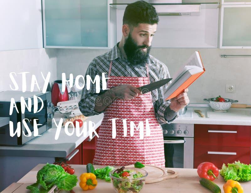 Cucinare l'uomo in cucina con un libro fotografie stock libere da diritti