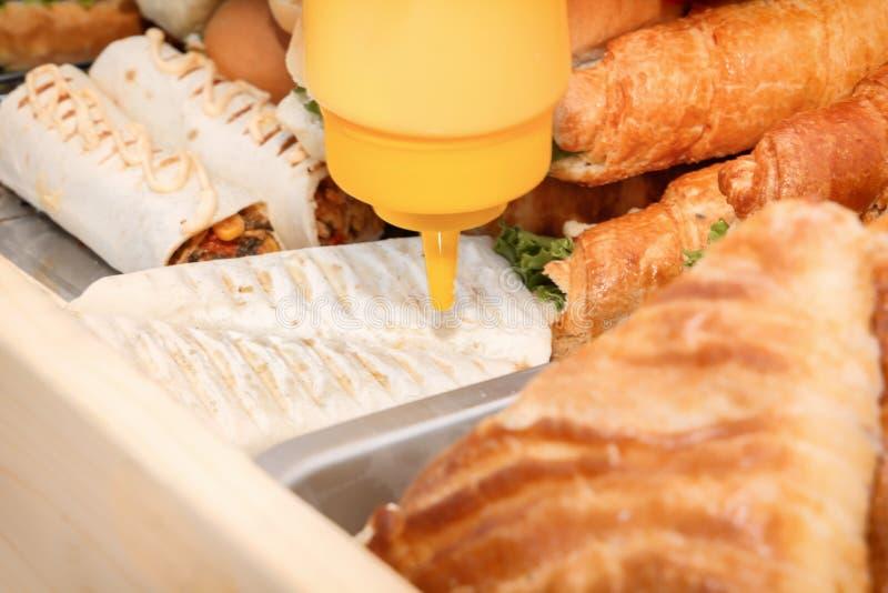 Cucini i panini e gli hamburger di versamento della via di pasto rapido della salsa sul contatore di un caffè immagine stock