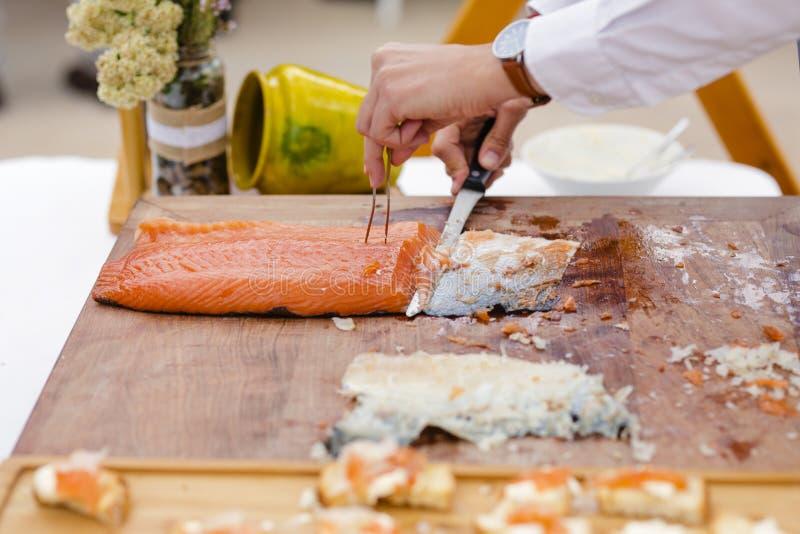 Cucini il taglio del pezzo di salmone immagine stock libera da diritti