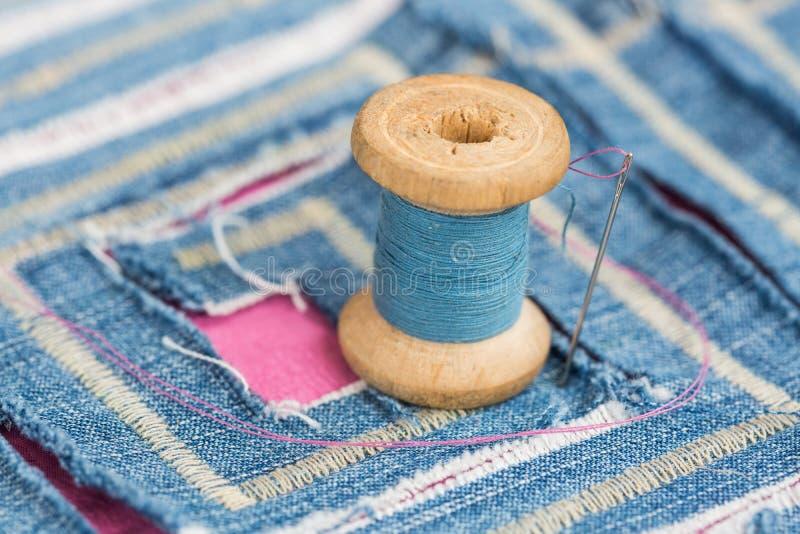 Cucito e concetto del ricamo - l'installazione di un ago e di una bobina del blu infila sopra tessuto blu decorato con il taglio fotografia stock libera da diritti