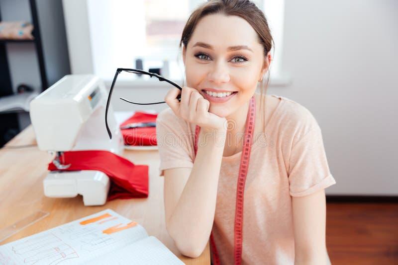 Cucitrice allegra della donna che si siede e che sorride sul lavoro fotografie stock