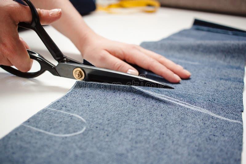 Cucitrice che lavora con il tessuto delle blue jeans fotografia stock