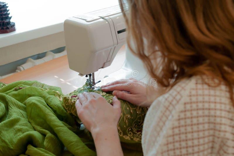 Cucitrice che si siede alla tavola con la macchina per cucire bianca e che lavora vicino alla finestra fotografia stock libera da diritti