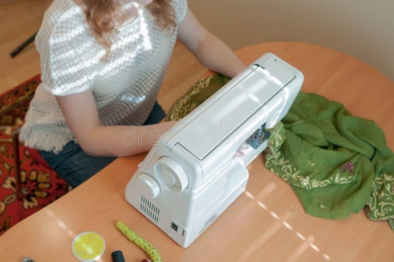 cucitrice che si siede alla tavola di legno ed alla macchina per cucire bianca, lavoranti vicino alla finestra fotografia stock