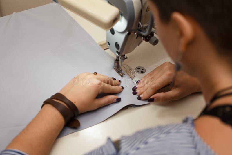 Cucitrice del posto di lavoro Adattamento dell'industria La ragazza cuce sulla macchina per cucire Abbigliamento della fabbrica immagine stock libera da diritti