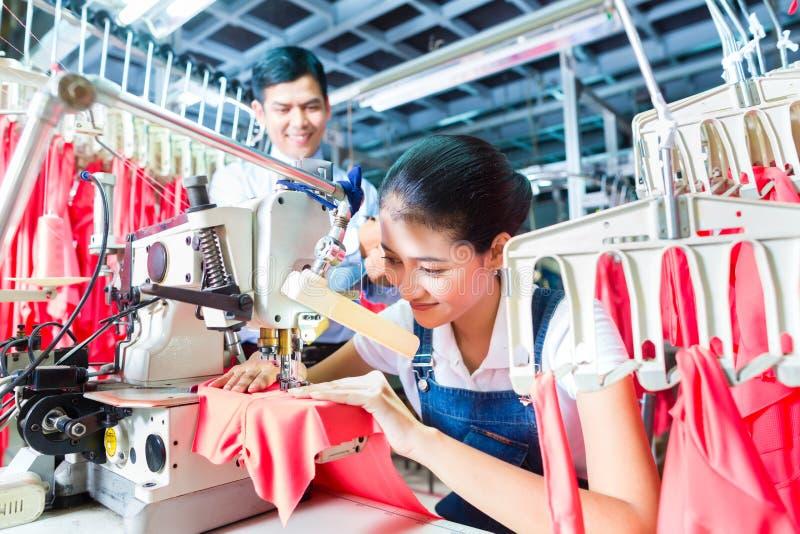 Cucitrice indonesiana nella fabbrica asiatica del tessuto fotografie stock