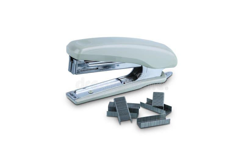 Cucitrice meccanica grigia fissa dell'ufficio con il mucchio delle graffette isolate su fondo bianco fotografia stock libera da diritti