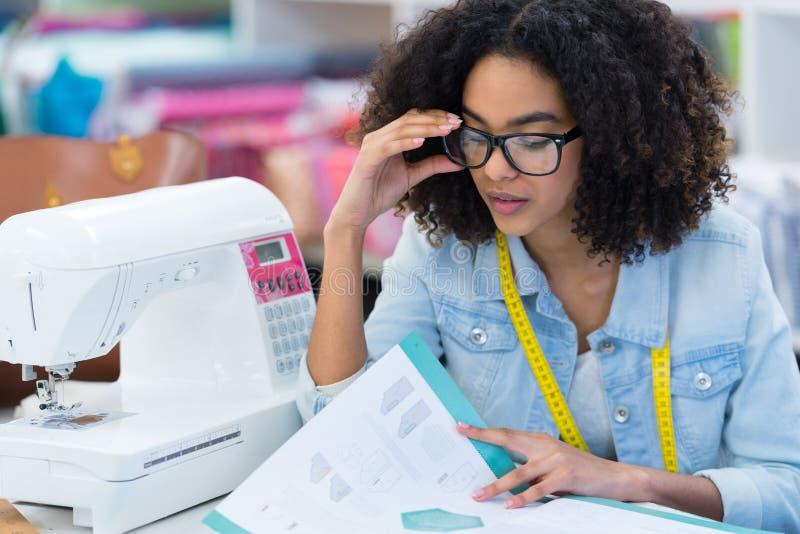 Cucitrice pensierosa della giovane donna che legge le note in taccuino immagini stock