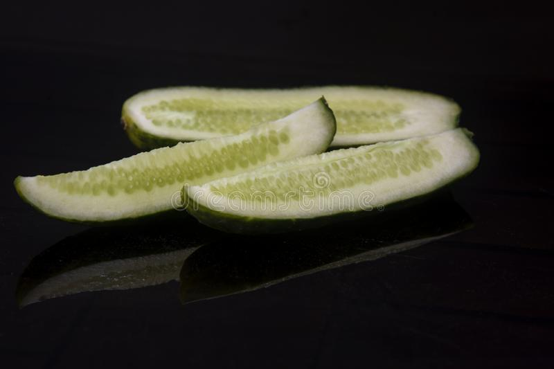 Cucumber cut on a dark background with interesting highlights stock photo