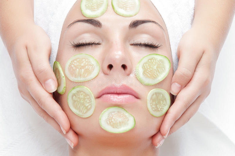 Cucumber face. Portrait of young beautiful woman being treated stock image