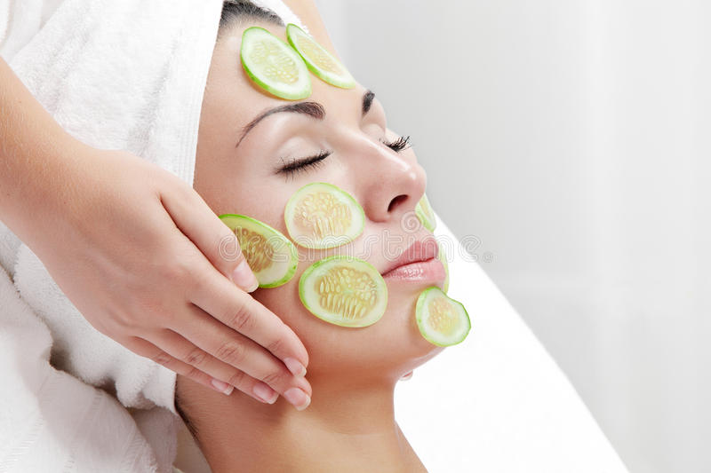 Cucumber face. Portrait of young beautiful woman being treated royalty free stock photo