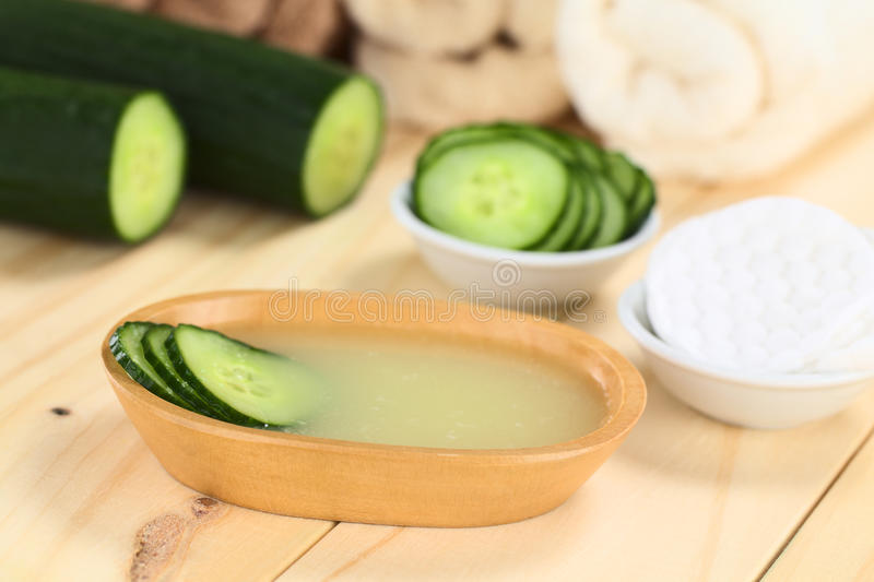 Cucumber Facial Toner. Homemade natural cucumber facial toner that hydrates, softens, soothes and cleanses the skin in a wooden bowl with cucumber slices, with royalty free stock photo