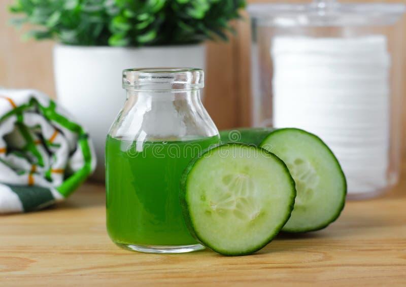 Cucumber juice in a small glass jar for preparing natural facial toner. Homemade cosmetics. Cucumber juice in a small glass jar for preparing facial toner stock photo